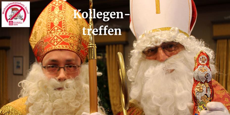 Zwei Nikoläuse mit Mitra, Bischofsstab, Gewand stehen nebeneinander und schauen in die Kamera. Der Nikolaus auf der rechten Seite hält den Schokonikolaus in der Hand.