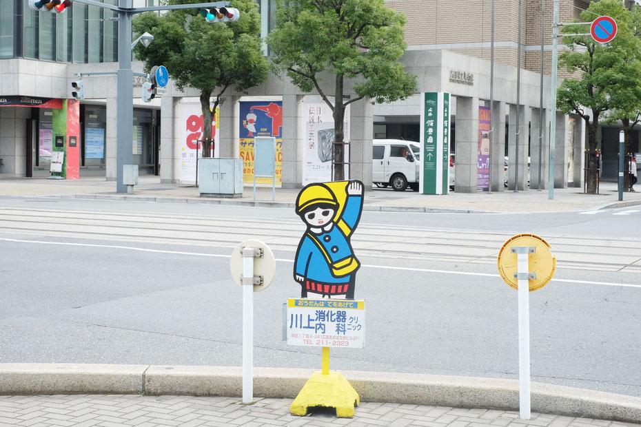 広島県立美術館前にある横断歩道に置かれた日静企画の広告看板まもりっこ