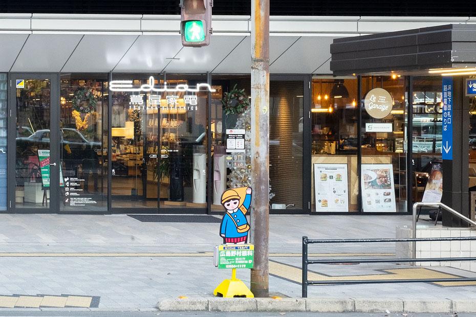 広島駅南口のエディオン蔦屋家電前にある横断歩道に置かれた日静企画の広告看板まもりっこ