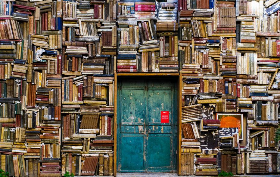 Türkise, alte Tür mit rotem Plakat, komplett umrahmt von einem Bücherregal mit übereinander liegenden alten Büchern und Magazinen