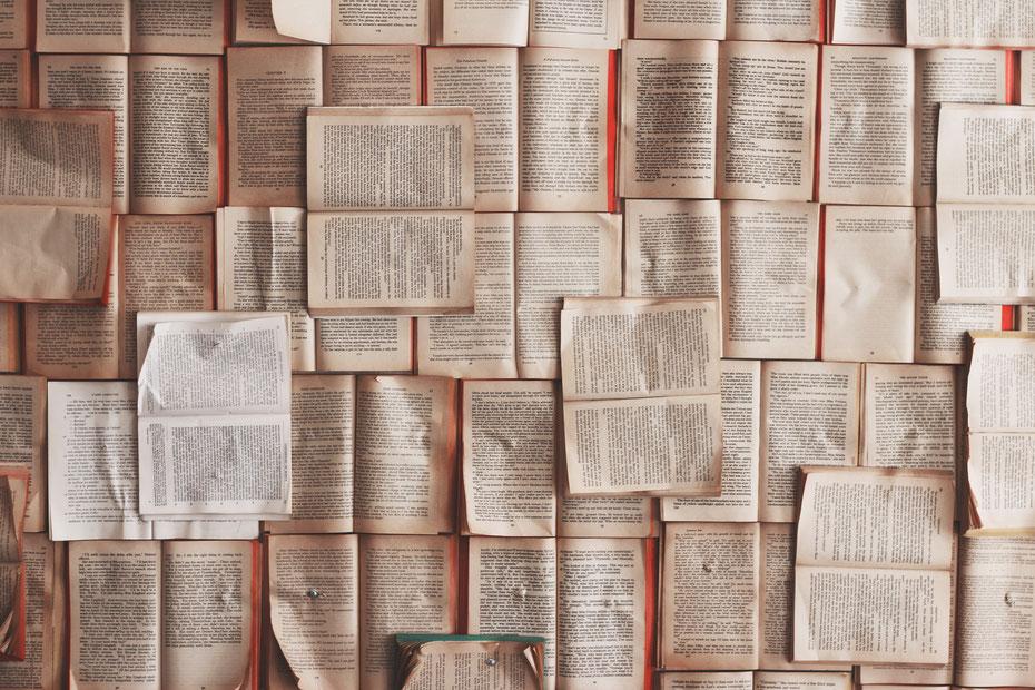 Bild zum Thema Publikation und Publishing. An die Wand gepinnte geöffnete Buchseiten, ohne Übergang aneinander gelegt wie ein Mosaik