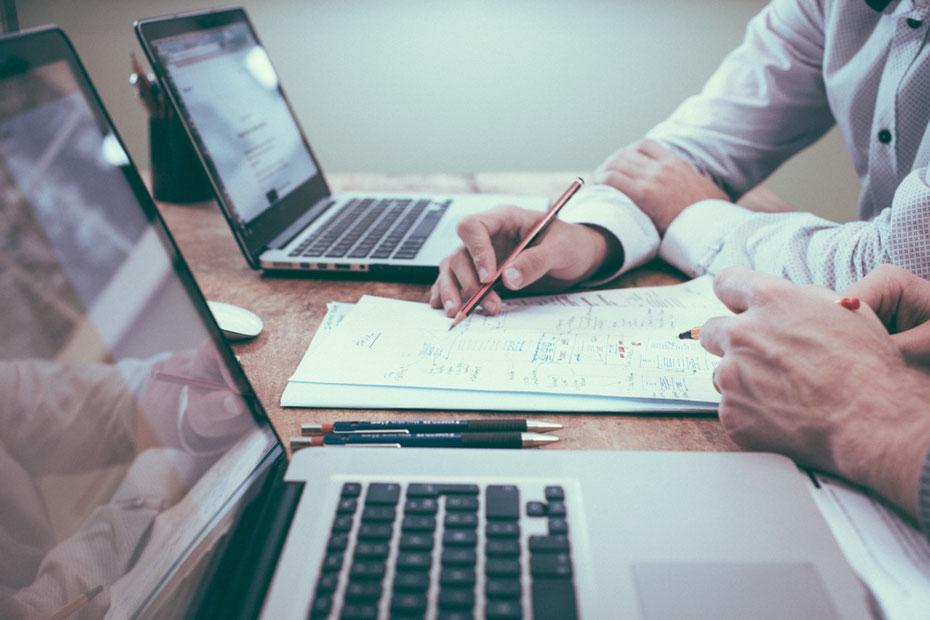 Teamwork-Situation, die Hände von zwei Personen mit geöffneten Stiften vor beschriebenem Blatt, dahinter zwei geöffnete Laptops mit