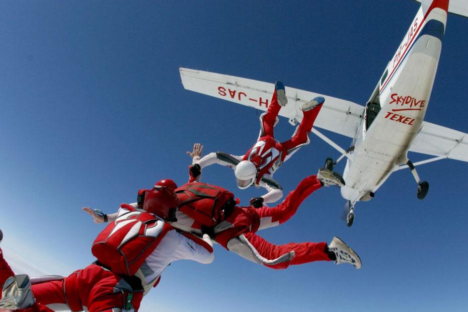 """<img src=""""image.jpg"""" alt=""""Drie parachutisten springen uit een vliegtuig hoog boven Texel voor een vrije val"""">"""