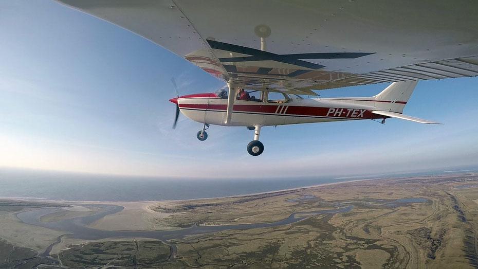 """<img src=""""image.jpg"""" alt=""""Een Cessna 172 vliegt boven de Slufter van Texel"""">"""