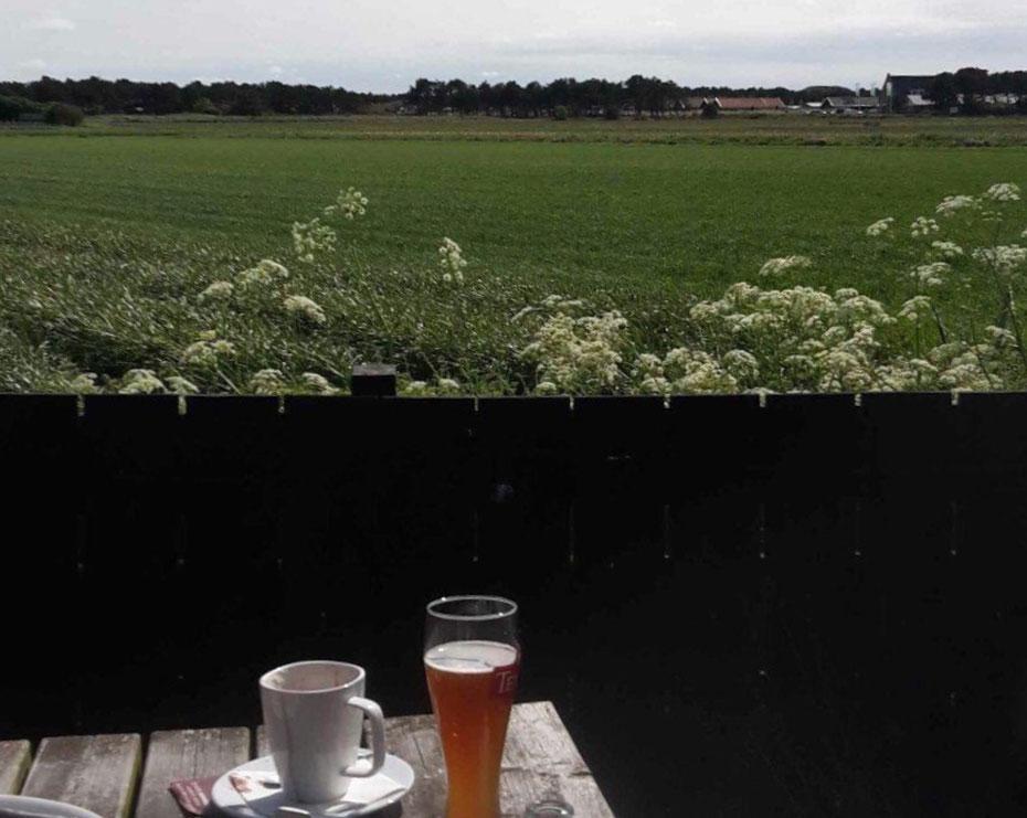"""<img src=""""image.jpg"""" alt=""""Terras aan de achterzijde van Klif23 met uitzicht op het aangrenzende weiland te Den Hoorn op Texel."""">"""