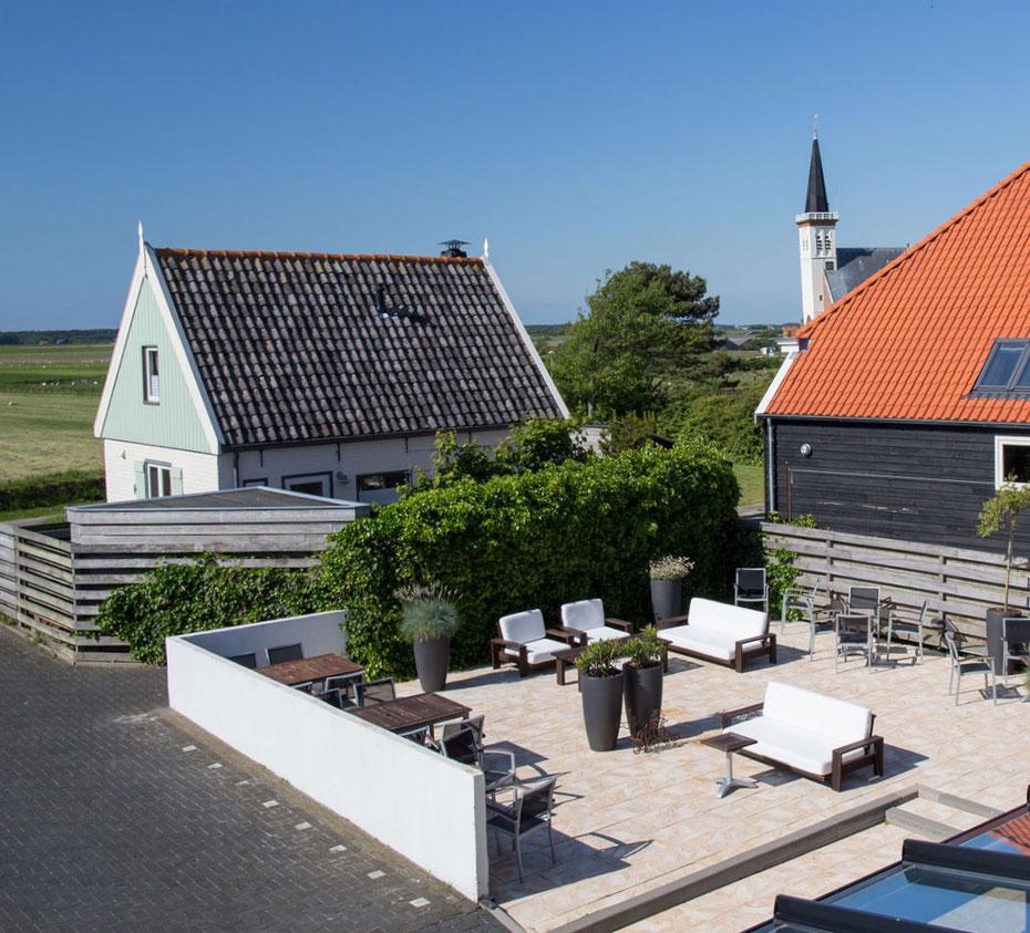 """<img src=""""image.jpg"""" alt=""""Het terras met parkeergelegenheid aan de achterzijde van restaurant """"Bij Jef"""" in Den Hoorn op Texel."""">"""