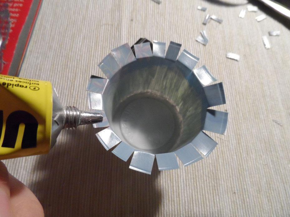 Schritt 9: Schneidet den oberen Rand mit einer Schere circa einen Zentimeter ein und schaut dann, ob der Becher in den Deckel passt. eventuell müsst ihr sonst die Seiten noch etwas kürzen. Bestreicht nun die Seiten mit Klebstoff