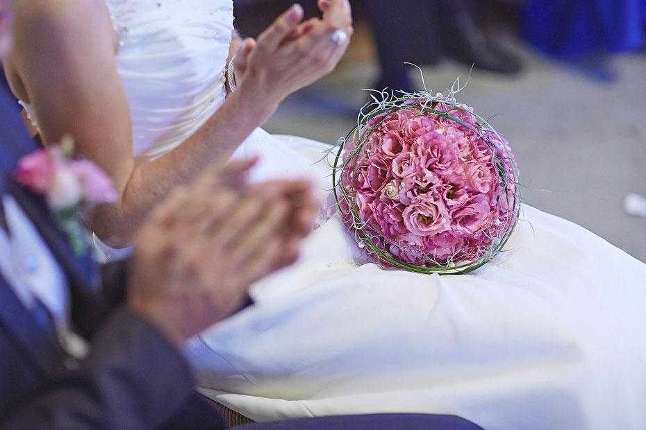 Ein Brautpaar sitzt in der Kirche. Zu sehen sind nur die Oberkörper und die Hände mit dem schönen Brautstrauss. Das Brautpaar klatscht in die Hände.