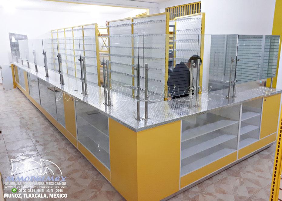 Mostrador para ferretería con cubierta de aluminio antiderrapante, entrepaños de melamina, frente de cristal y mampara protectora en la cubierta con postes de acero inoxidable y vidrio templado