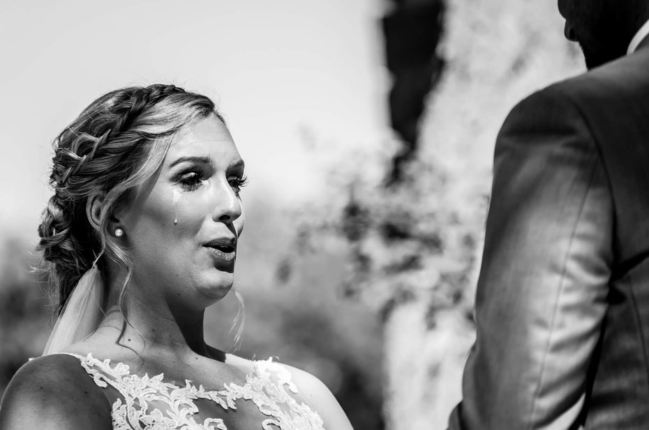 Black and white photo of a bride and groom. Bride is exhaling with a tear rolling down her cheek. Groom is visible from behind.
