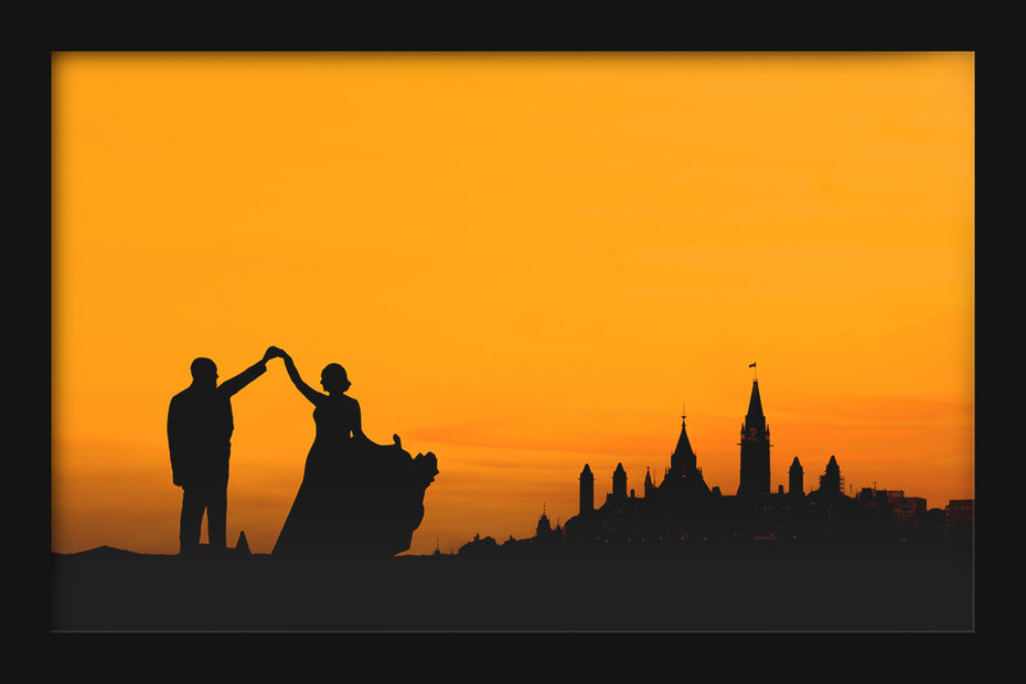 Wedding couple in silhouette dancing in front of Parliament hill in Ottawa. She is wearing a dress he is wearing a suit. Sky is orange.