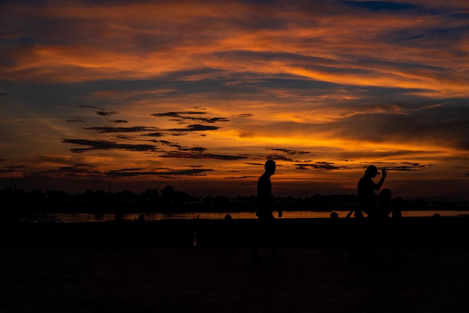 """Ein Sonnenuntergang am Mekong, der """"Mutter aller Flüsse"""" ist immer ein spektakuläres Motiv. Das ruhige Vientiane lädt gerade dazu ein die letzten Sonnenstrahlen auf der Uferpromenade mit einem kühlen Beerlao in der Hand zu genießen."""