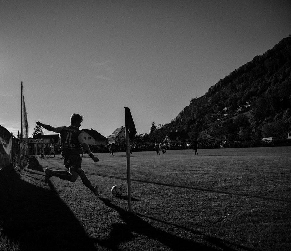In der Vorarlbergliga gibt es nicht nur guten Fussball zu sehen, sondern auch einzigartige Photomotive wie hier in Kennelbach. Im schönsten Abendlicht vor dem Pfänderrücken schlägt der Spieler die Ecke in den Strafraum, vor dem wartenden Photographen.