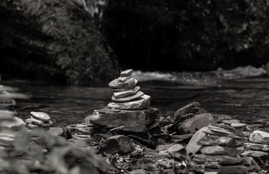 Immer wieder stehen am Fluss aufgetürmte Steine. Diese stehen stellvertretend für einen Stupa an dem Ort und sind verstorbenen Familienangehörigen gewidmet.