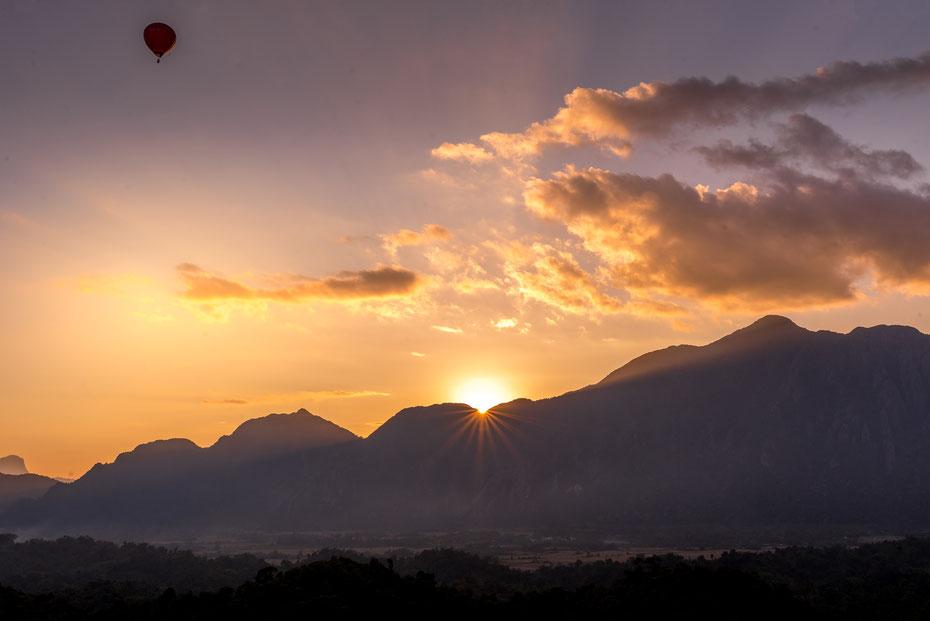 Nham Xay Viewpoint - an solchen Viewpoints fehlt es rund um Vang Vieng gewiss nicht. Der steile Aufstieg wurde durch diesen Sonnenuntergang belohnt. Und als Bonus kam auch noch ein Heissluftballon vorbei.