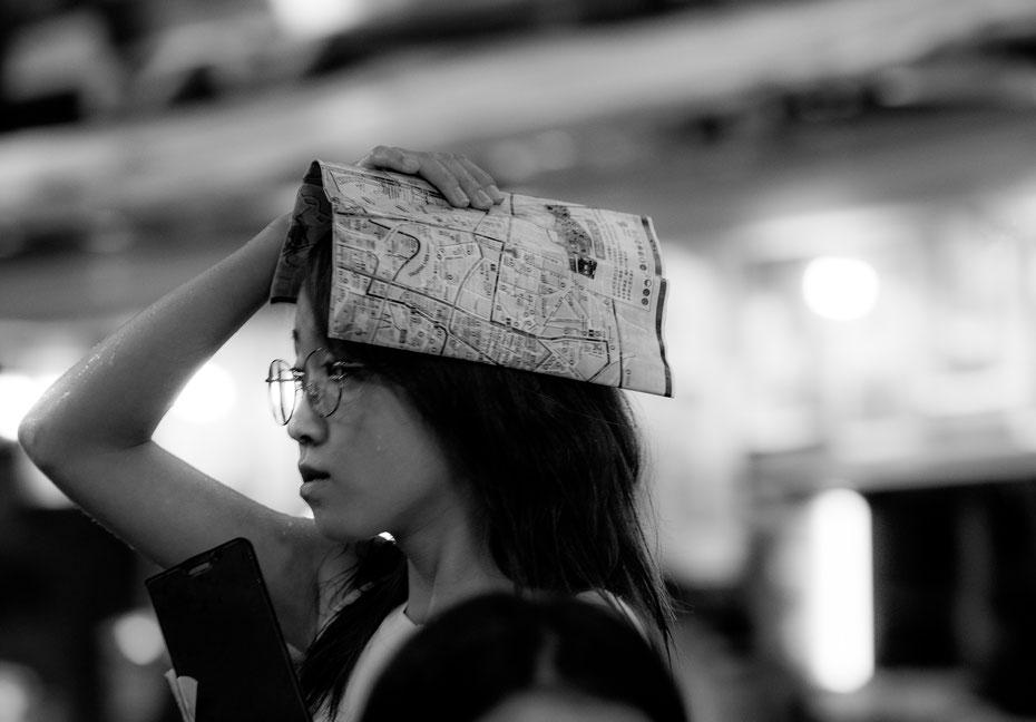 Schutz vor dem täglichen Regenschauer in Singapur. Bei der Touristin muss der Stadtplan herhalten.