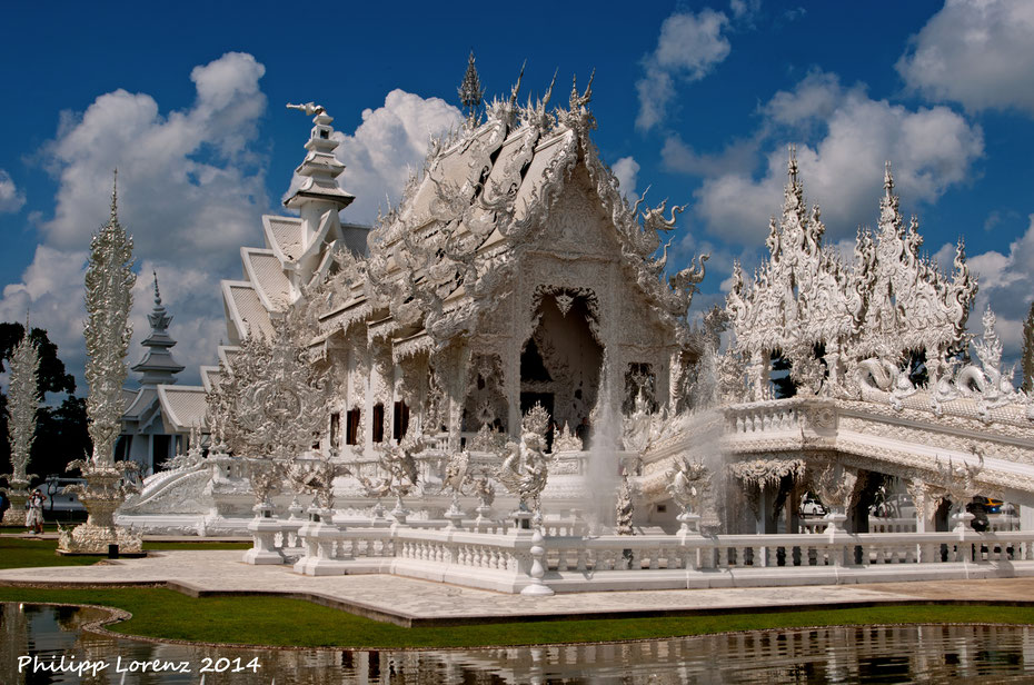 """Eine tolle Abwechslung zu den traditionellen Tempeln ist der """"weisse Tempel"""" in der Nähe von Chiang Rai, ganz im Norden des Landes. Ein ortsansässiger Künstler gestaltete die Tempelanlage mit vielen modernen Einflüssen, vor allem im Innern."""