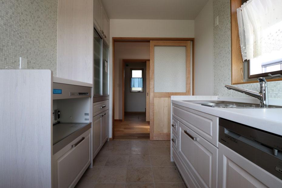 キッチンから玄関と納戸を眺めた様子。キッチンに置ききれない物は納戸にも収納できる。