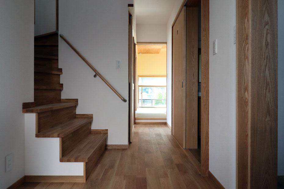 玄関から和室方向を見る。右手には納戸と洗面室。左手には二階へ続く階段が見えている。