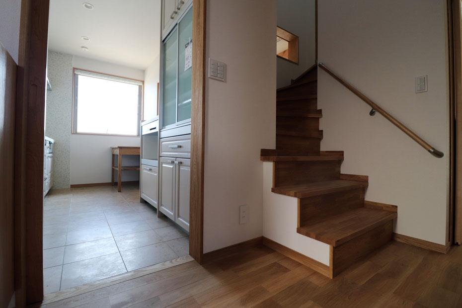 玄関からキッチンと階段を見る。キッチン南側にある大型の滑り出し窓によって明るいキッチン。階段途中にはダイニングを見下ろす小窓を設置している。
