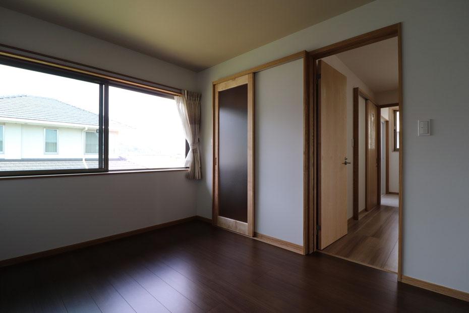 二階北西角の部屋。北側には部屋幅いっぱいの引違窓を設置。中央引戸はウォークインクローゼットの入口。