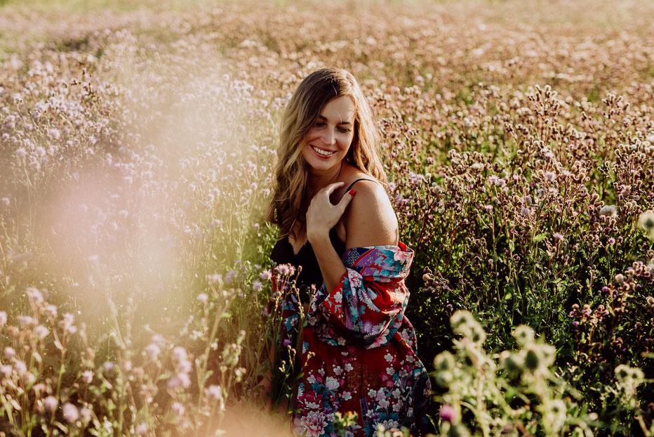 Frau sitzt lächelnd in einem Feld voller Blumen bei Mainz
