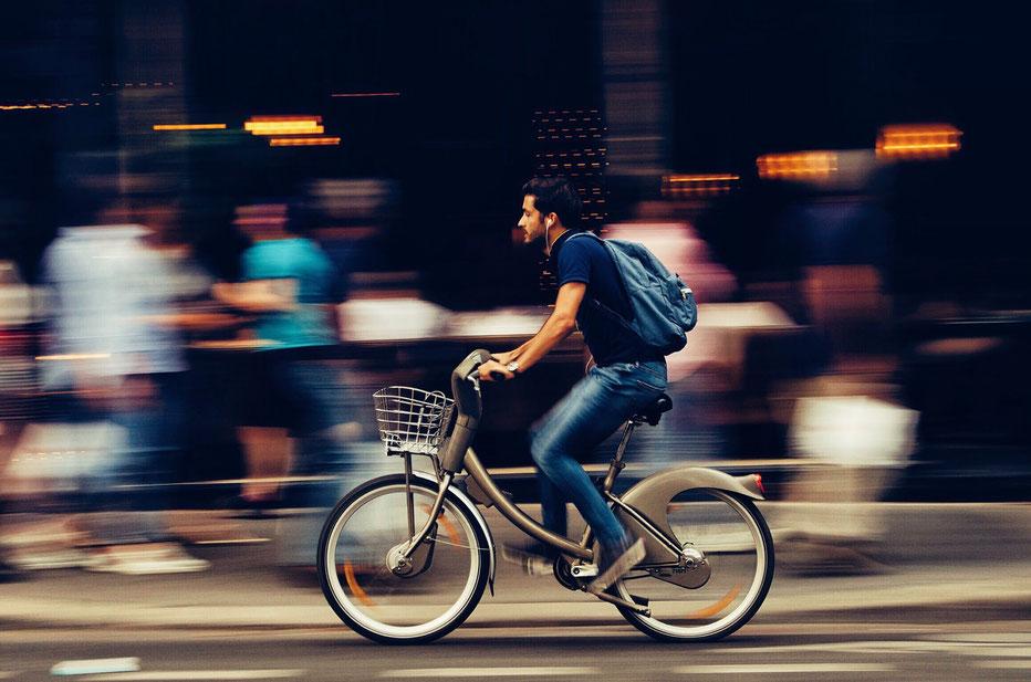 Mann auf Fahrrad fährt durch die Stadt