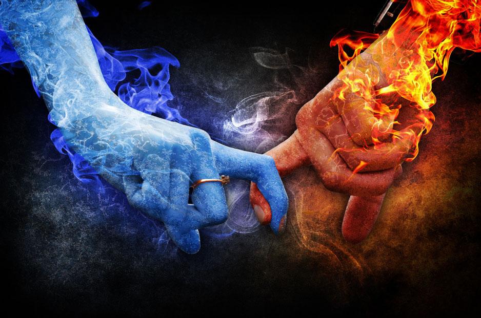 zwei Haende in rot und blauen Flammen miteinander verbunden