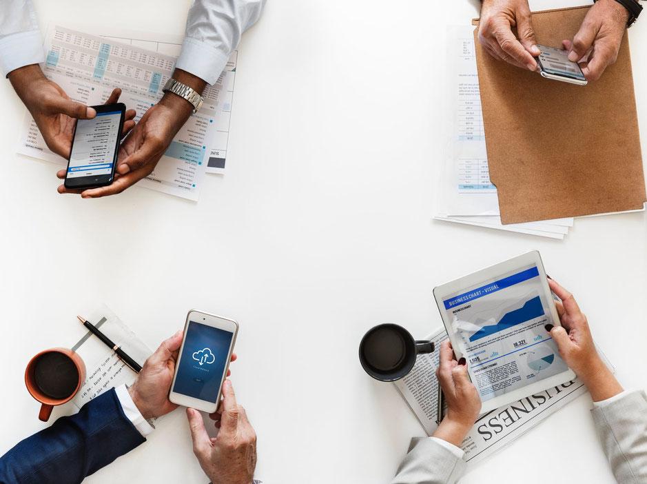 4 Personen mit Smartphone und Tablet