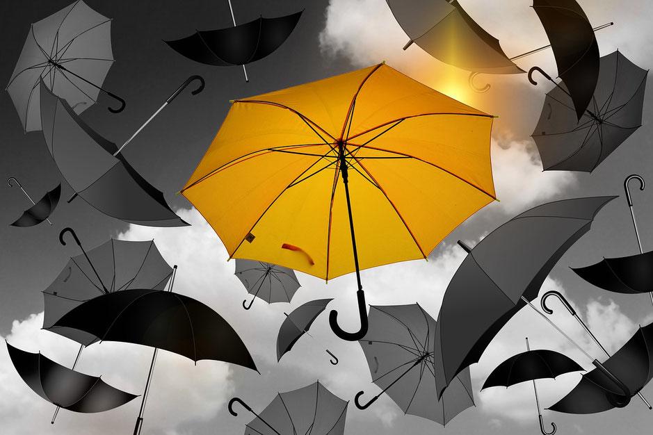 Gelber Regenschirm und mehrere schwarze Regenschirme