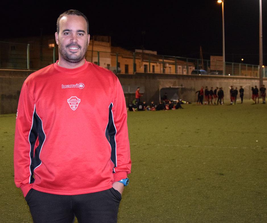 Imagen de un hombre de 30 años en un campo de fútbol. Vestido con sudadera roja y pantalón negro. Sonríe. Al fondo, muchos jugadores entrenando.