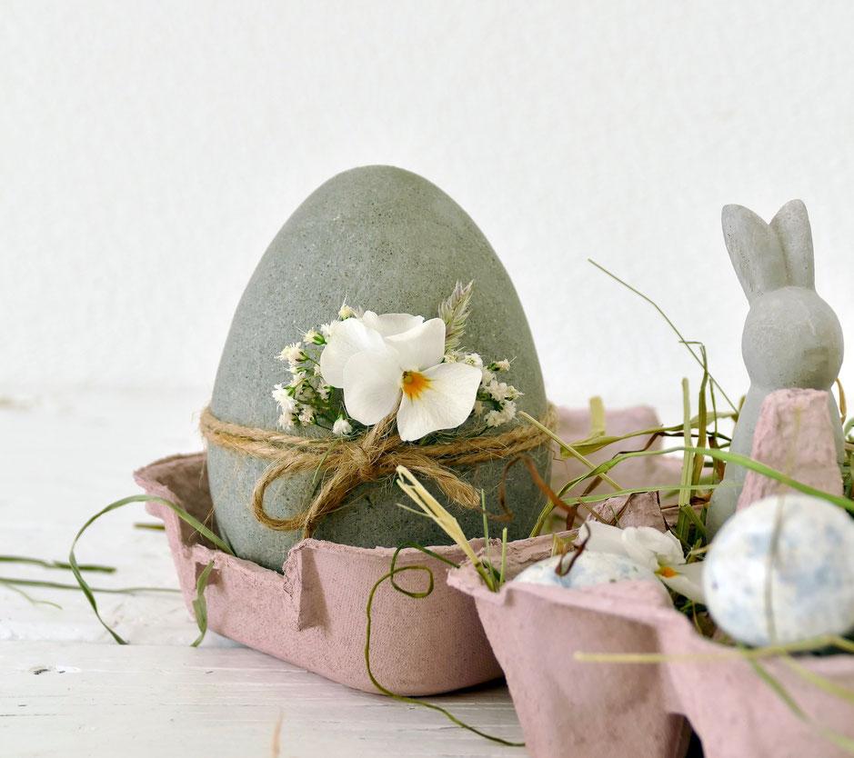 DIY Beton Osterei mit weisser Blume in rosa Eierschachtel mit Heu und kleinen Eiern
