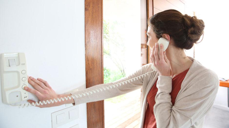 Frau öffnet Tür über Gegensprechanlage