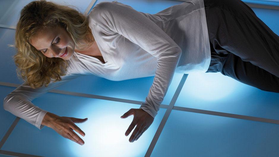 Frau fühlt Wärme aus Elektroheizsystem