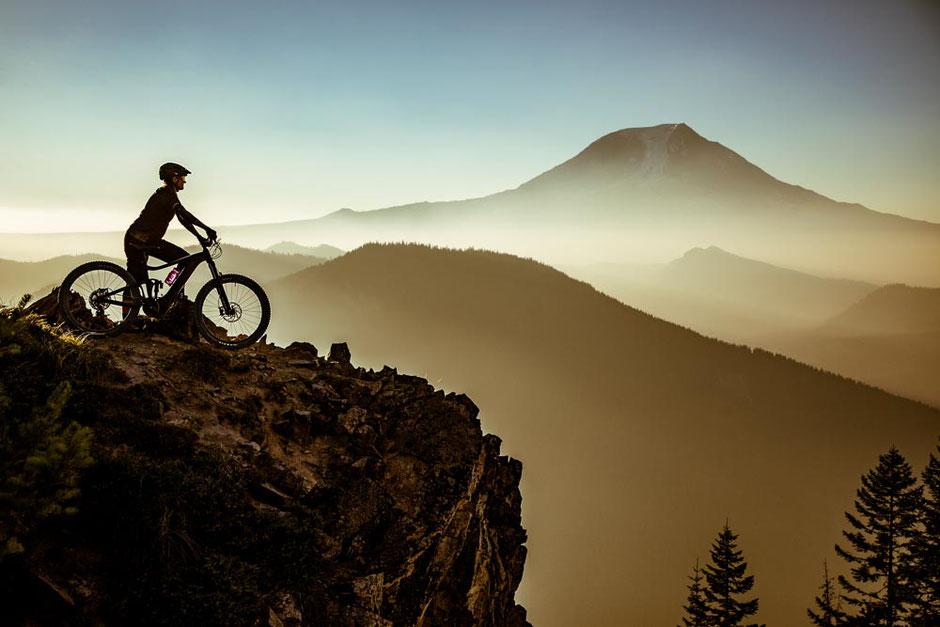Eine Frau auf dem Liv Intrigue X E+ mit Aussicht auf Berge