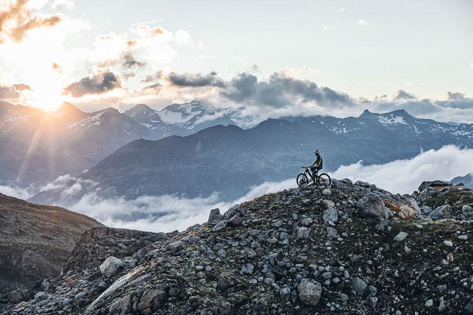 Mann mit Husqvarna e-Mountainbike auf Schotter in den Bergen