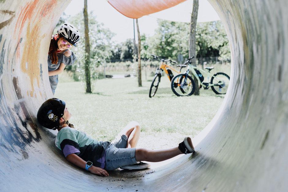 2 Kinder beim spielen vor e-Mountainbikes von R Raymon