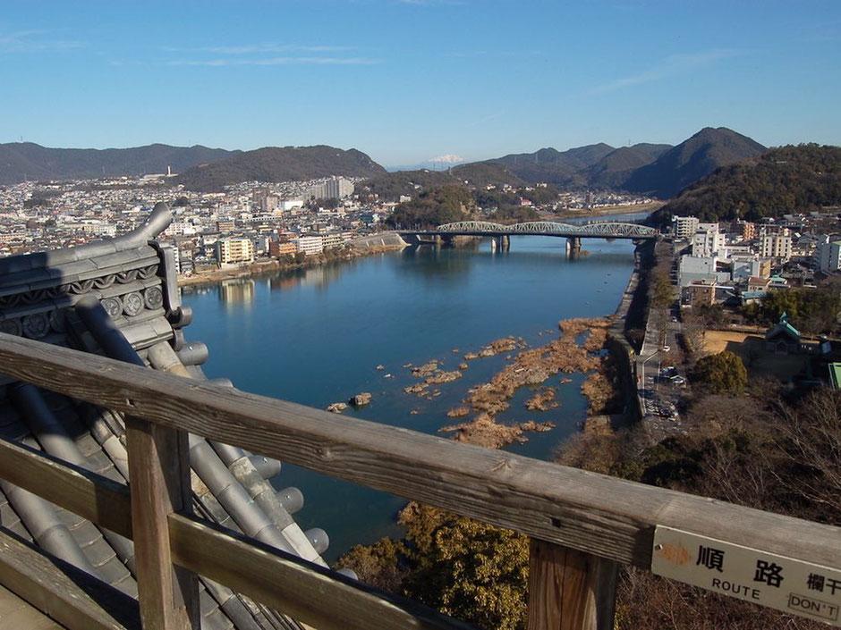 犬山城の天守から木曽川を眺める。遠くには雪を冠った御嶽山の姿も