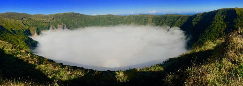 Drei besondere Naturerlebnisse auf einem Foto: Die Caldera voller Nebel, ein kreisrunder Regenbogen und eine tagaktive Fledermaus