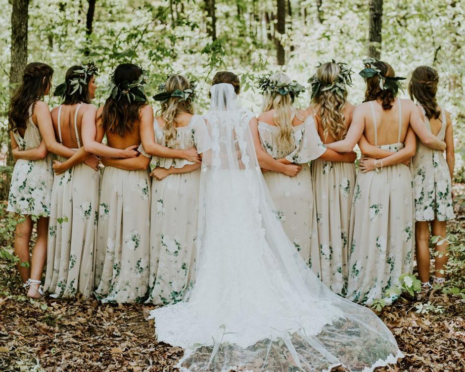 Mariée et ses demoiselle d'honneur enlacées dans les bois, coiffées de couronnes de fleurs et feuillage d'olivier. Article de blog sur lasymbolique du mariage par La cinquieme saison.