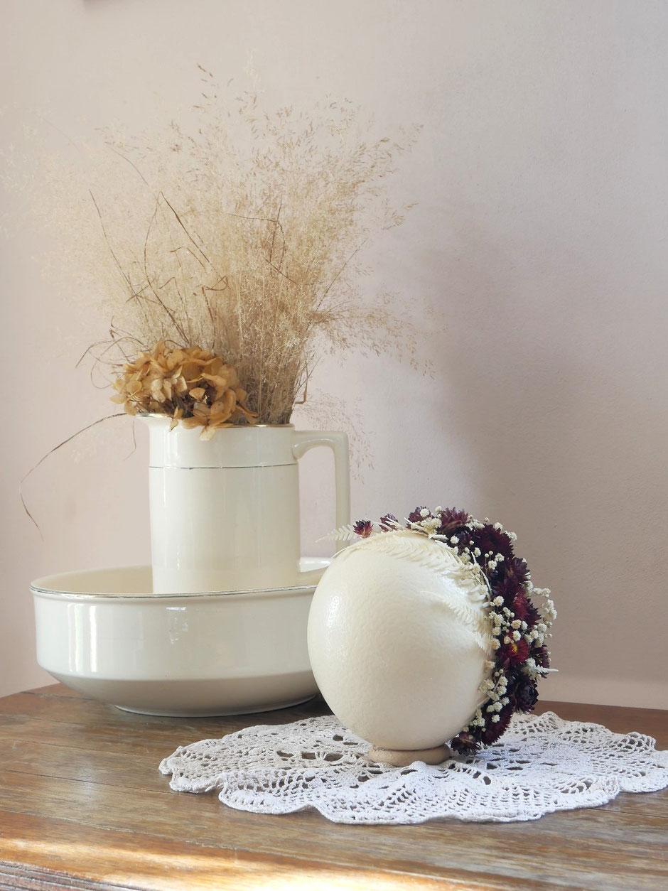Véritable oeuf d'autruche décoré de fleurs séchées et stabilisées. Pièce unique de la cinquième saison, dans les teintes de crème, ivoire et bordeaux. Composition : oeuf d'autruche, fleurs d'immortelles, gypsophile et fougère blanche.