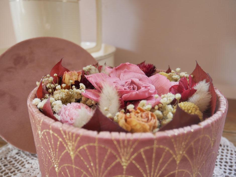 Boite ronde en velours, garnie de fleurs séchées et stabilisées, créations de la cinquième saison. Teintes de vieux rose, bordeaux et doré. Fleurs séchées pour la décoration.