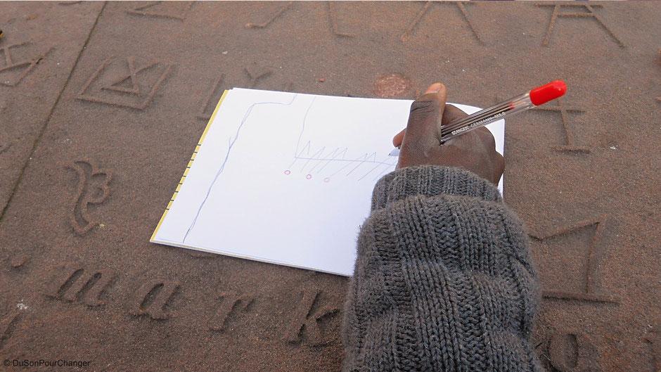 enfant réalise croquis de la Cathédrale sur ouvrage en gres marques de tacherons strasbourg du son pour changer