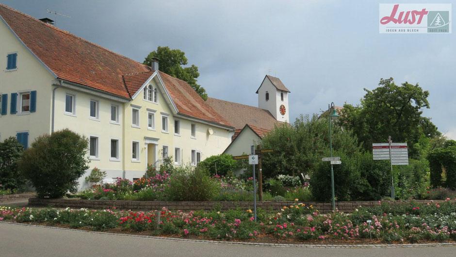Das Rosendorf Nöggenschwiel lässt sich bequem zu Fuß erkunden und in einem Kiosk findet man Schönes und Nützliches rund um die Rose.