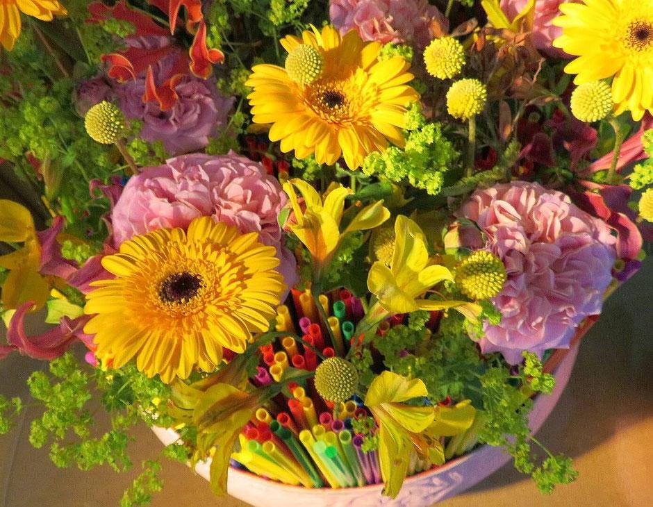 Verschiedene Blütenfarben und -formen machen das Blumengesteck spannend. Gewagt zu gelber Gerbera und Inkalilie sind rosafarbene, gefüllte Rosen.