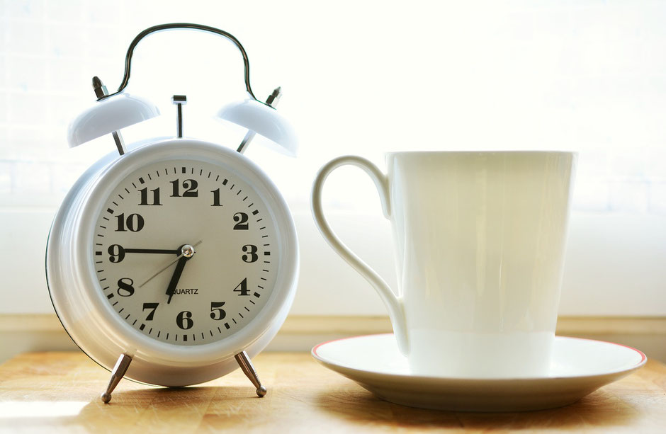Coffee cup with an analogue clock next to it