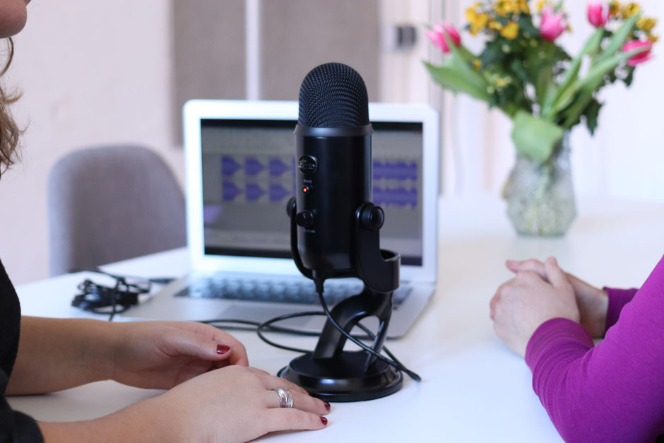 two women talking with a microphone for a podcast