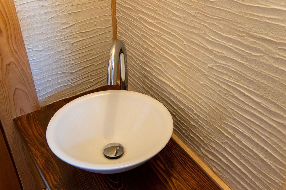 洗面台と趣のある剣先仕上げの左官壁を見る