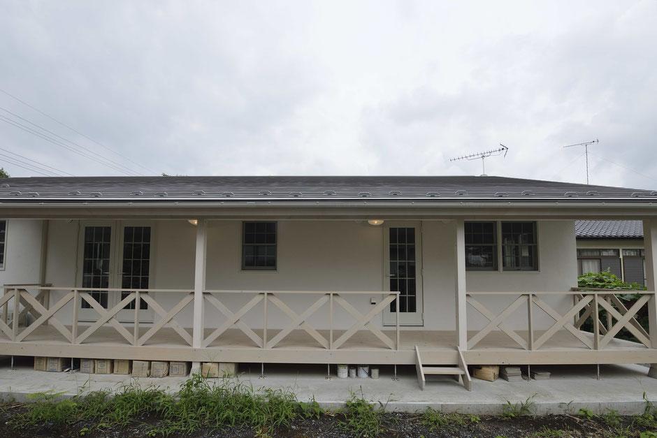 デッキのある平屋の家の庭から白色のデッキを眺める