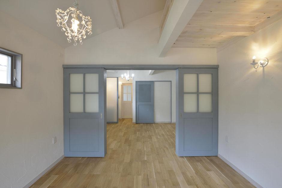 デッキのある平屋の家の夫婦の部屋は水色の戸が際立つ